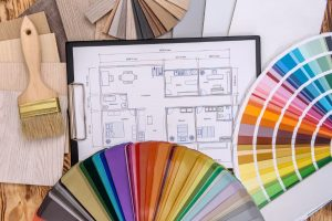 tabletop covered with design sketches, color wheels and a paint brush